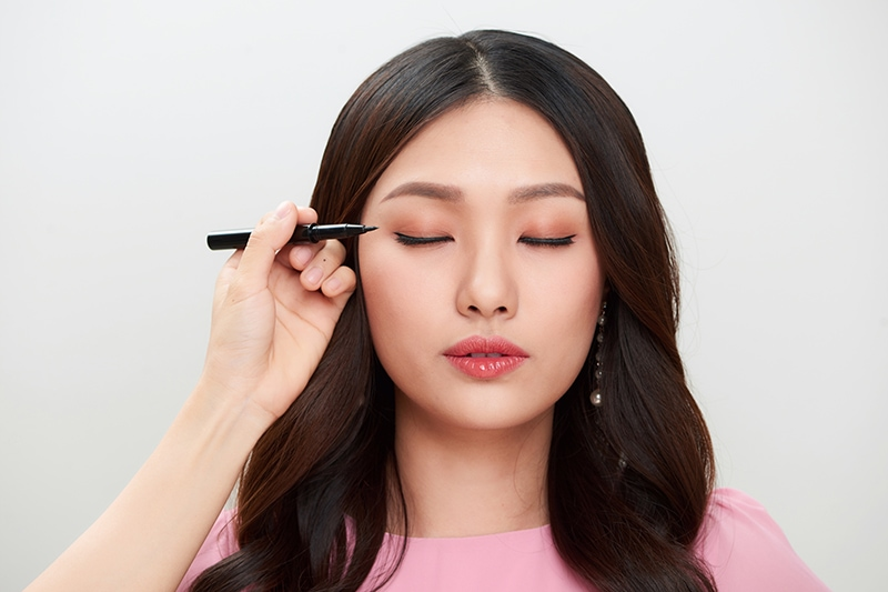 Beautiful young asian woman make-up with black eyeliner.