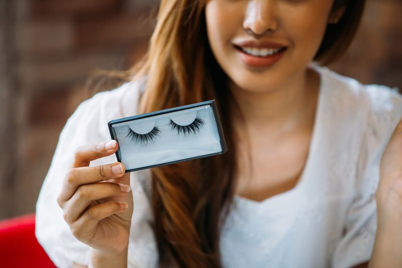 cropped model showing decorative eyelashes in box
