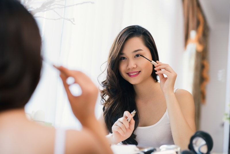 Beautiful asian woman applying mascara in front of big mirror